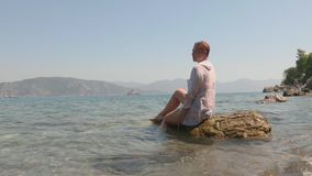 Relaxed woman in white wet tunic sitting on stone in sea waves. Happy tourist woman sitting on rock in sea water and. Enjoying waves in sunny day stock video footage
