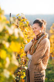 Relaxed woman winegrower standing in vineyard outdoors in autumn. Portrait of relaxed brown-haired woman winegrower walking in vineyard outdoors in autumn. Small Stock Photography