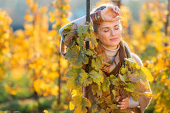 Relaxed woman winegrower standing in vineyard outdoors in autumn. Portrait of relaxed young brown-haired woman winegrower standing in vineyard outdoors in autumn Stock Photography