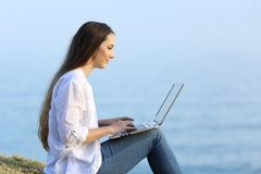Relaxed woman writing in a laptop on the beach. Side view portrait of a relaxed woman writing in a laptop on the beach Royalty Free Stock Image