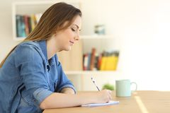 Relaxed woman writing a note on a notebook. E view portrait of a relaxed woman writing a note on a notebook Royalty Free Stock Image
