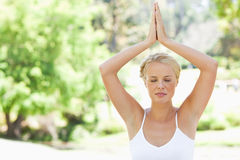 Relaxed woman in a yoga position in the park Stock Photo