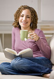 Relaxed women enjoying reading a book Stock Photos