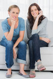 Relaxed women posing while sitting on the couch Royalty Free Stock Images