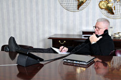 Relaxed at Work. A senior businessman relaxed with his feet up while taking notes from a business phone conversation in the conference room Royalty Free Stock Photography