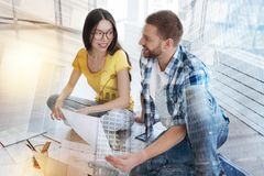 Relaxed worker looking at his pretty colleague Stock Image