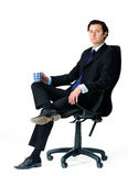 Relaxed worker in office chair. Male office worker seats in his chair, holding a mug of coffee Stock Image