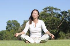 Relaxed yoga meditating mature woman Royalty Free Stock Photo