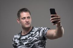 Relaxed young adult male holding mobile phone and taking photos or selfie stock image