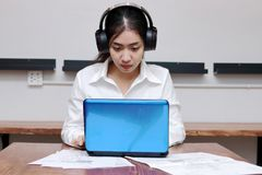Relaxed young Asian business woman with headphones working with laptop in office. Royalty Free Stock Photo