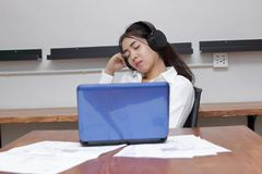 Relaxed young Asian business woman listening music with eyes closed in workplace. Relaxed young Asian business woman listening music with eyes closed in stock photography