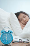 Relaxed of young Asian woman sleeping on bed in winter. Retro alarm clock and glasses on foreground Royalty Free Stock Photos