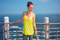 Relaxed young athlete in fitness outfit standing at embankment Stock Photos