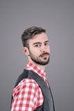 Relaxed young bearded hipster side view looking at camera Royalty Free Stock Images