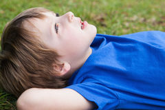 Relaxed young boy lying at park. Close-up side view of a relaxed young boy lying at the park Royalty Free Stock Images