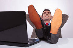 Relaxed young business man looks up with hands behind head Royalty Free Stock Photography
