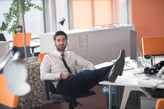 Relaxed young business man at office Royalty Free Stock Image