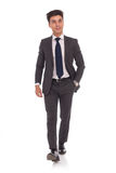 Relaxed young business man is walking with hand in pocket Royalty Free Stock Photos