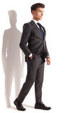 Relaxed young business man walking. In studio near white wall Stock Photos