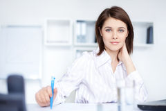 Relaxed young business woman woman in office. Closeup of relaxed young beautiful business woman smiling at office Royalty Free Stock Image