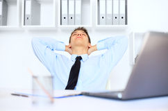 Relaxed young businessman in office royalty free stock image