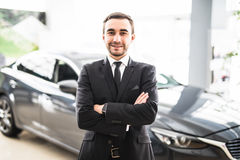 Relaxed young businessman or salesman with hands crossed in front of car Royalty Free Stock Image