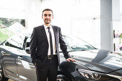 Relaxed young businessman or salesman with hands crossed in front of car Stock Photography