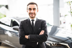 Relaxed young businessman or salesman with hands crossed in front of car Stock Images