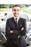 Relaxed young businessman or salesman with hands crossed in front of car Stock Image