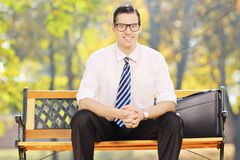 Relaxed young businessman sitting on a bench and looking at came. Ra in a park Royalty Free Stock Images