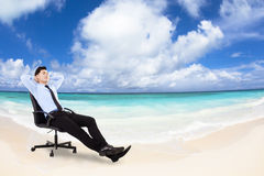 Relaxed Young businessman sitting in  chair. Relaxed Young businessman sitting in a chair with beach background Royalty Free Stock Image