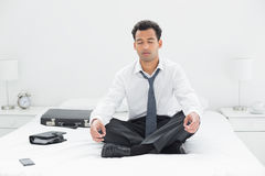 Relaxed young businessman sitting in lotus pose on bed Stock Images
