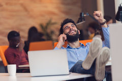 Relaxed young businessman at workplace at early morning, relaxing. Royalty Free Stock Photography