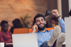 Relaxed young businessman at workplace at early morning, relaxing. Relaxed young businessman at workplace at early morning, relaxing, at modern startup office Stock Image
