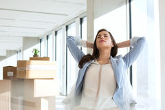 Relaxed young businesswoman with hands behind head in new office stock photos
