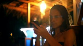 Relaxed young businesswoman smiles using smartphone e-commerce app at summer night lounge beach cafe enjoying nightlife. Successful local woman using social stock footage