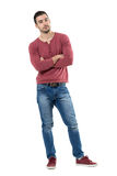 Relaxed young casual man with crossed arms leaning and looking at camera. royalty free stock images