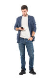 Relaxed young casual man in denim shirt and jeans typing message on cellular phone. Royalty Free Stock Photography