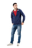 Relaxed young cool man in blue sweatshirt with hands in back pockets looking behind. Full body length portrait isolated over white studio background Stock Images