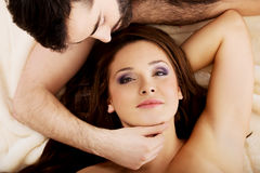 Relaxed young couple lying in bed. Royalty Free Stock Images