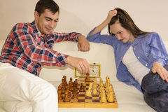 Relaxed young couple playing chess at home lying on sofa. won - Friendship. Royalty Free Stock Images