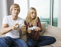 Relaxed young couple playing video game in living room at home Stock Images