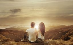 Relaxed couple watching a sunset stock photos