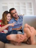 Relaxed young couple working on laptop computer at home Stock Images