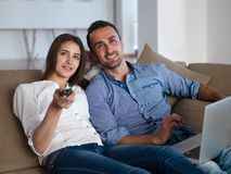 Relaxed young couple working on laptop computer at home Stock Photos