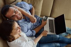 Relaxed young couple working on laptop computer at home Royalty Free Stock Images