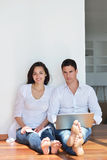 Relaxed young couple working on laptop computer at home Royalty Free Stock Photography