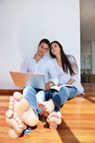Relaxed young couple working on laptop computer at home Stock Photography