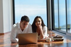 Relaxed young couple working on laptop computer at home Stock Photo