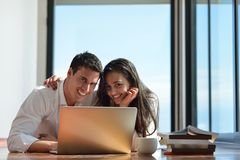 Relaxed young couple working on laptop computer at home Royalty Free Stock Image